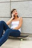 Localización de la chica joven en el monopatín en la ciudad con el móvil Foto de archivo libre de regalías