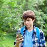 Localización feliz del adolescente en hierba en parque Fotos de archivo