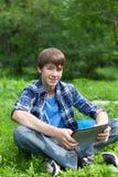 Localización feliz del adolescente en hierba en parque Imagen de archivo libre de regalías