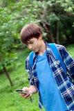 Localización feliz del adolescente en hierba en parque Imagenes de archivo