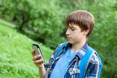Localización feliz del adolescente en hierba en parque Fotografía de archivo libre de regalías
