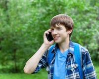 Localización feliz del adolescente en hierba en parque Foto de archivo