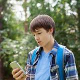 Localización feliz del adolescente en hierba en parque Fotografía de archivo