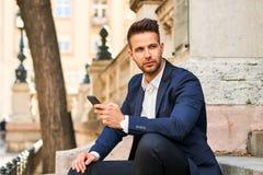 Localización joven del hombre de negocios en las escaleras y usar su teléfono imagen de archivo