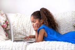 Localización negra del adolescente en un sofá con un ordenador portátil Fotos de archivo