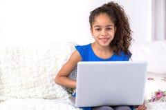 Localización negra del adolescente en un sofá con un ordenador portátil Imagenes de archivo