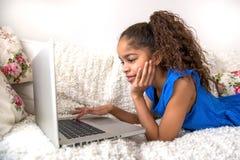 Localización negra del adolescente en un sofá con un ordenador portátil Imagen de archivo libre de regalías