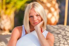 Localización rubia de la mujer en el deckchair, disfrutando de vacaciones de verano foto de archivo