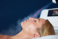 Localized cryotherapy on woman face Stock Image