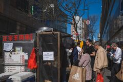 Locals buying barbeque at street food vendor in Flushing Chinatown