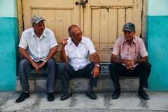 3 locals having a chat in the shade in Havana, Cuba. 3 locals having a talk in the shade in Havana, Cuba royalty free stock photo