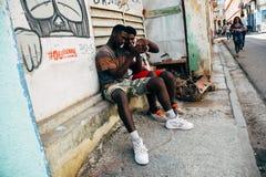 2 locals looking at their smart phone in Havana, Cuba. 2 locals looking at a smart phone in Havana, Cuba stock photos