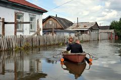 Locals move around the streets by boat. The Ob river, which came out of the banks, flooded the outskirts of the city. BARNAUL, RUSSIA - JUNE 26, 2010: Locals Royalty Free Stock Images