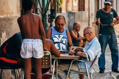 Locals playing dominoes in Havana city, Cuba. Locals playing dominoes street side in Havana city, Cuba royalty free stock image