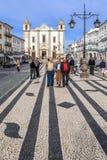 Locals que dan un paseo en Giraldo Square con el pavimento portugués típico del guijarro y Santo Antao Church imágenes de archivo libres de regalías