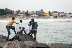 Locals relaxing at Mahabalipuram beach. Group of local men relaxing and watching the activities happening at the beach. Mahabalipuram, Tamil Nadu Stock Image