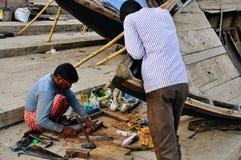 Locals repair a boat in Varanasi, India. Locals repairing their boat in Varanasi, India royalty free stock images