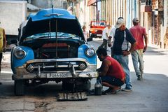 Locals repairing their old classic car in Havana, Cuba. royalty free stock image