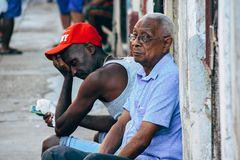 2 locals sitting in Havana city, Cuba. 2 locals sitting in the hot weather in Havana city, Cuba royalty free stock photo