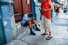 Locals sitting on the streets in Cuba. Locals sitting on the streets to cool off from the hot sun in Havana, Cuba royalty free stock image