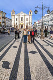 Locals strolling in the Giraldo Square with the typical Portuguese cobblestone pavement and the Santo Antao Church Royalty Free Stock Images