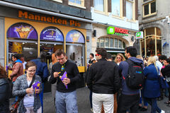 Locals and tourist at Amsterdam's famous Manneken pis dutch fries Royalty Free Stock Images