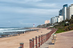 Locals and tourists on the beach near the Millennium Pier and lighthouse in Umhlanga Rocks Stock Photography