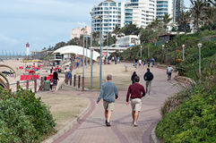 Locals and tourists on the beach near the Millennium Pier and lighthouse in Umhlanga Rocks Stock Photo