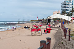 Locals and tourists on the beach near the Millennium Pier and lighthouse in Umhlanga Rocks Stock Image