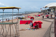 Locals and tourists on the beach near the Millennium Pier and lighthouse in Umhlanga Rocks Stock Images