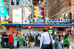Locals and tourists going about their business in busy Times Square outside of the NYPD Times Square Precinct. stock image