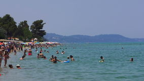 Locals and tourists on a Greek beach on a hot day.