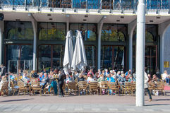 Locals and tourists have drinks in outdoor cafe on Rembrandtplein, the Netherlands. Stock Photo