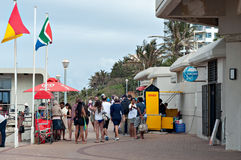 Locals and tourists on the promenade near the Millennium Pier and lighthouse at Umhlanga Rocks beach Stock Photo
