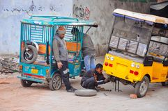 Locals try to repair a tuk tuk in Delhi, India. royalty free stock photos