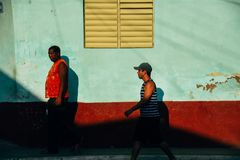Locals walk in the afternoon sun in Trinidad, Cuba. 2 locals walk in the afternoon sunset in Trinidad, Cuba royalty free stock photography