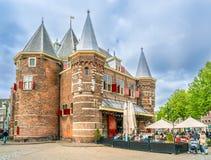 Locals y turistas que comen y que beben adentro en un restaurante situado en el cuadrado de Nieuwmarkt en la casa vieja de la esc foto de archivo