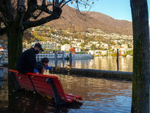 Locarno, Father and son playing throw the leaves in water. Stock Image