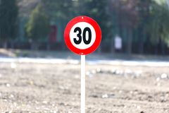 Located on the Edge of the Red Metal and Outdoors Road Speed Sign royalty free stock photography