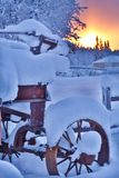 Winter Sunrise behind a snow-covered old, rusty wagon stock images