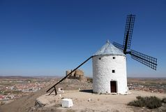 White Windmill and castle on hill in Consuegra, Spain. Located about 60km from Toledo, Consuegra is a lovely historic town set against a range of low mountains stock images