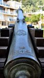 Ancient cannon directed to modern building. Located near maritime museum the ancient warship cannon is directed towards a modern building appearing against it stock image