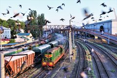 A  moving train heads towards the Odessa station, overflown by a group of seagulls stock images