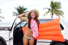 Location de voiture : femme heureuse et son véhicule près de la plage photos libres de droits