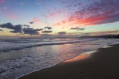 Location place Agia Marina Beach, island Crete, Greece. Sea coast spangled by rocks, the sunrise is reflecting on the wet sand. stock images