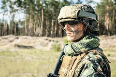 US Marine Soldier. Location shot of United States Marine with rifle weapons in uniforms. Military equipment, army helmet, warpaint, smoked dirty face, tactical Royalty Free Stock Photo