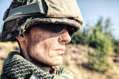 US Marine Soldier. Location shot of United States Marine with rifle weapons in uniforms. Military equipment, army helmet, warpaint, smoked dirty face, tactical Stock Photo