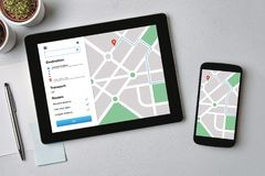 Location tracker concept on tablet and smartphone screen. GPS ma. Location tracker concept on tablet and smartphone screen over gray table. GPS map navigation royalty free stock image