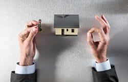Location, vente ou achat à la maison avec la clé dans des mains décontractées image stock