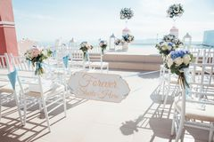 The location of the wedding ceremony on the island of Santorini. With white chairs decorated with bouquets of flowers Royalty Free Stock Image